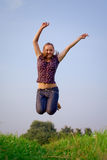 Jumping girl. Young joyful girl jumping on blue sky Stock Photo