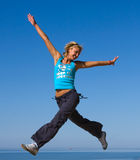 Jumping girl. Blue sky high Royalty Free Stock Photography