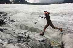Jumping girl across the ice  crack in glacier Stock Photography