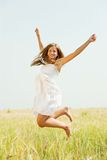 Jumping girl  at cereals field. In summer Stock Photos