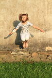 Jumping girl. Cute little kid - blond girl in white clothes jumping in front of dirty grey wall Royalty Free Stock Photos