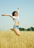 Jumping girl  at  field. Jumping girl  at cereals field in summer Stock Photo