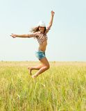 Jumping girl  at  field. Jumping girl  at cereals field in summer Royalty Free Stock Image