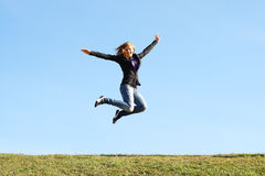 Jumping girl at field in summer. Freedom stock image