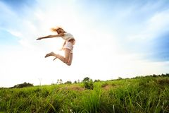 Jumping girl at field in summer Stock Photos