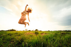 Jumping girl at field in summer Royalty Free Stock Photography
