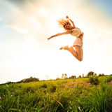 Jumping girl at field in summer Royalty Free Stock Photos