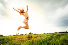 Jumping girl at field in summer Stock Photo