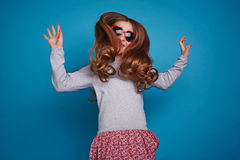 Jumping girl in the glasses. Girl in red heart-shaped glasses jumping Royalty Free Stock Photo