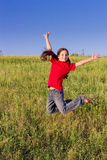 Jumping girl on green field Stock Image
