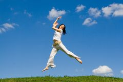 Jumping girl in meadow Stock Images
