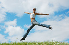 Jumping girl on meadow. Jumping girl on a green meadow Royalty Free Stock Photography
