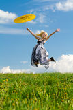 Jumping girl with parasol on meadow. Jumping young girl win yellow parasol on meadow in spring royalty free stock photos