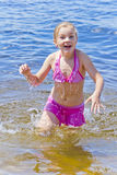 Jumping girl in pink swimsuit stock image