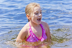 Jumping girl in pink swimsuit stock photos