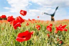 Jumping girl in poppy field. Focus on poppy Royalty Free Stock Image