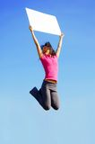 Jumping Girl With Sign. Girl jumping with sign in front of a big blue sky royalty free stock photo
