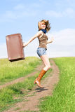 Jumping girl with a suitcase Stock Photo