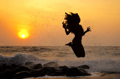 Jumping girl ( sunset ) Stock Images