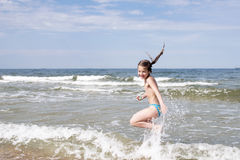 Jumping girl in surf. Child girl have fun jumping in sea surf by bright sunny day Stock Images