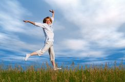 Jumping girl under clouds Stock Photography