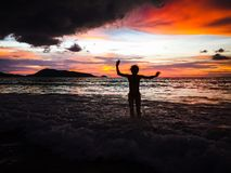 Jumping girl. In the water at sunset Royalty Free Stock Images