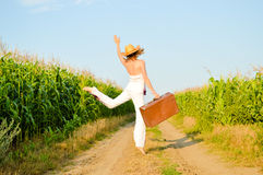 Jumping girl wearing hat with suitcase on road in Royalty Free Stock Image