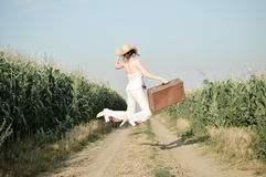 Jumping girl wearing straw hat with suitcase in Royalty Free Stock Image