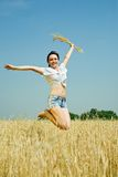 Jumping girl  with  wheat ear. At  field in summer Royalty Free Stock Photo