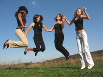 Jumping girls. Beautiful women jumping altogether hand in hand Royalty Free Stock Photos
