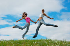 Jumping girls. On the green meadow stock image