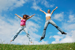 Jumping girls. On the green meadow stock images