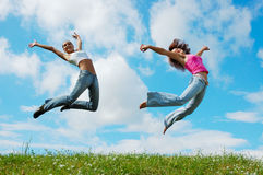 Jumping girls. On the green meadow royalty free stock photography