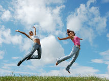 Jumping girls. On the green meadow royalty free stock image