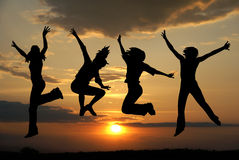 Jumping girls. On sunset background Stock Photo
