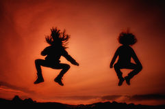 Jumping girls having fun at sunset Royalty Free Stock Images