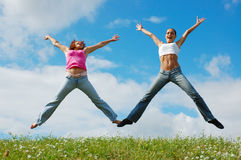 Jumping girls on meadow. Jumping girls on a background blue sky royalty free stock photo