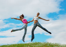 Jumping girls on meadow. Jumping girls on the green meadow royalty free stock images