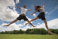 Jumping in the grass. A cute couple having fun jumping in the outdoors, on green grass Stock Photo