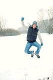 Jumping handsome young man in winter. Fashion portrait of excited jumping handsome young man enjoying himself in winter Royalty Free Stock Image