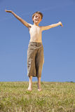 Jumping happy boy. A smiling and happy eight years old jumping boy, photographed in the summer sun with blue sky in the background Royalty Free Stock Photos