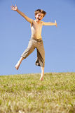 Jumping happy boy. A laughing and happy eight years old jumping boy, photographed in the summer sun with blue sky in the background Stock Photos