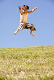 Jumping happy boy. A laughing and happy eight years old jumping boy, photographed in the summer sun with blue sky in the background Stock Image