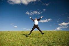 Jumping happy businessman. Jumping Businessman in meadow - green grass and blue sky Royalty Free Stock Image