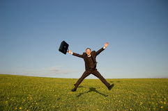 Jumping happy businessman. Jumping Businessman in meadow - green grass and blue sky Stock Image