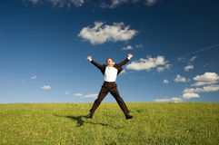 Jumping happy businessman. Jumping Businessman in meadow - green grass and blue sky Stock Images