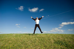 Jumping happy businessman. Jumping Businessman in meadow - green grass and blue sky Stock Photos