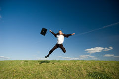 Jumping happy businessman. Jumping Businessman in meadow - green grass and blue sky Royalty Free Stock Photo