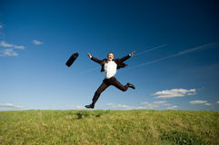 Jumping happy businessman. Jumping Businessman in meadow - green grass and blue sky Stock Photography