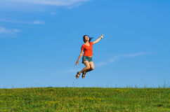 Jumping happy emotion woman on grass and sky backgrounds Royalty Free Stock Photo